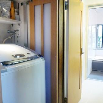 工事後:洗濯機は洗面所入り口脇に設け、急な来客にも隠す事が出来る様収納扉を設けている。 照明は消費電力や熱線量が少ないLED照明を採用している。