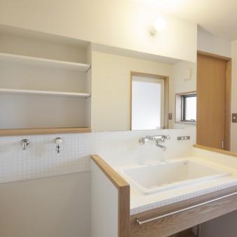 12:洗面所(親) 台所、WICへと通じる洗面所により、ストレスの無い回遊性のある動線を確保している。