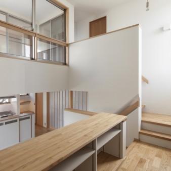 26:ワークルーム(子) スキップしたワークルームから半階ずれた台所、バルコニーを見る。レベルで緩やかに領域を分けている。