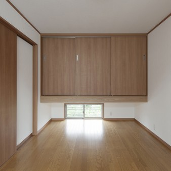 13:寝室 床を撫でる風が地窓から流れてくる。地窓の先には隣宅の緑が茂っている。