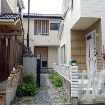 1:外観 隣地に住宅が建ち並ぶ旗竿敷地のアプローチを見る。