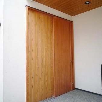 3:ポーチ 昼間のポーチ。玄関戸はピーラー材で製作している。 床は砂利洗い出し。天井は杉の無垢板。