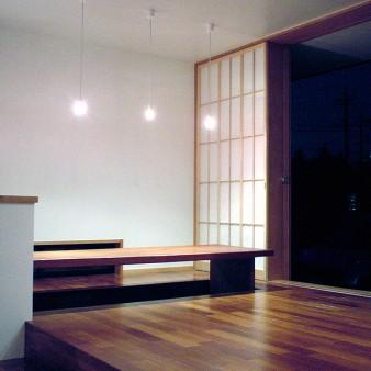 9:居間 木製建具を全開にした居間夜景。 床はケンパスの無垢フローリングで床暖房を施している。