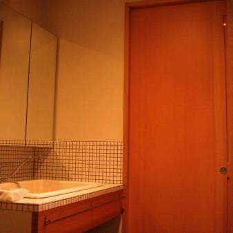 8:洗面所 洗面台は陶器製のシンクと25㎜のタイルの組み合わせ 正面の扉はトイレ。 戸先に溝を彫る事で引き手とし、上部に孔を開ける事でドアスコープとしている。