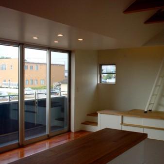 9:居間 台所よりテラス越しに風景を望む