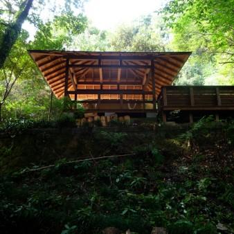 2:屋根架構 歴史を感じさせる石垣の下から屋根を見上げる。屋根架構は骨太な傘を広げた様な原始的な空間
