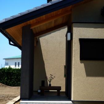 2:ポーチ 光が中庭に差し込む。屋根は和瓦。天井は杉の無垢板。外壁はジョリパットと土壁の様な質感のせっ器質タイル。