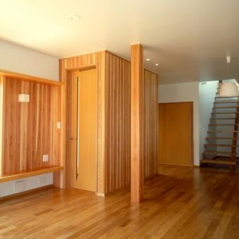 7:居間 居間から階段室を見る。階段室の上部から外の光が漏れる。独立柱は杉の150㎜角。壁は杉の無垢板と塗装仕上げ。天井は塗装仕上げ。床はタモの無垢フローリングで床暖房を施している。