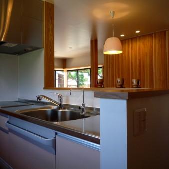 8:台所 台所から食堂を見る。背面には食器棚。両脇には土間と食品庫を適所に設けてる。