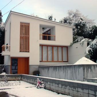 4:冬 竣工当時の冬の全景。 敷地の特性を活かし、床レベルが半階ずつスキップし、落ち葉や雪を素直に落とす為、単純な1枚の屋根が架かっている。