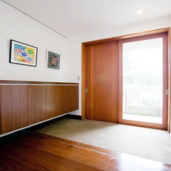 7:玄関 半地下の玄関。玄関戸はピーラー材で製作し、土間は砂利洗い出し仕上げとしている。 壁、天井は漆喰塗り。床はチークの無垢フローリング。