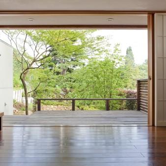 10:居間 居間から縁側を見る。居間と庭が一体になり、自然を身近に感じる様に、建具は天井高さに合わせた木製引き分け戸とした。 壁、天井は漆喰塗り。床はチークの無垢フローリングで床暖房を施している。