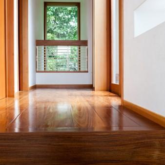 16:階段室 アトリエからの階段を上がり東面を見る。床は板目の美しい、チークの無垢フローリング。 窓は隣地の緑で満たされている。