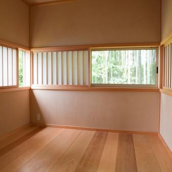 18:書斎 書斎北面。床は和室より100㎜上がり、天井高さを2100㎜とする事で重心の低い空間となっている。 読み書きしながら景色も楽しめる様に、開口部の高さを決定し、パノラマの様に窓を設けている。 壁、天井は京壁。床板は、桧、サワラ、ヒバ、タモ、ピーラー、桜と多様な無垢板を30㎜に加工している。