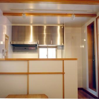 8:台所 食堂より台所を見る。 カウンターは食器棚も兼ねている。