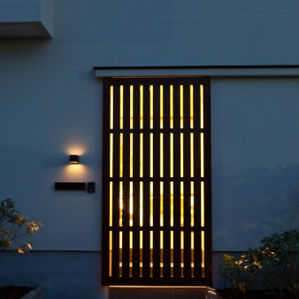 1:格子戸 夜、桧で製作された格子戸を道路から眺める。ポーチの光りが格子戸の隙間より放射状の光になり道路を照らす。